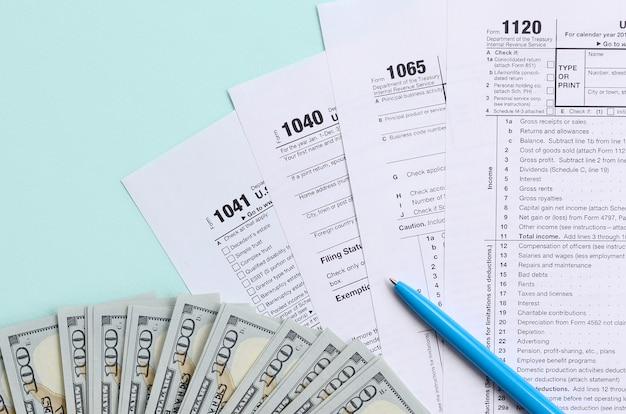 Formularze podatkowe leżą w pobliżu stu dolarowych banknotów i niebieskiego pióra na jasnoniebieskim tle.