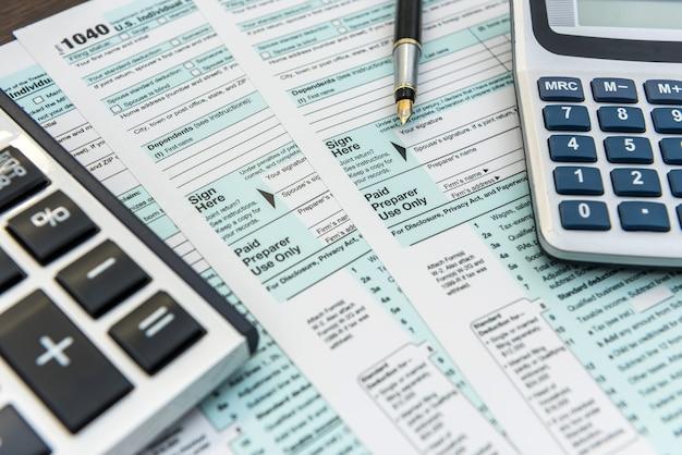 Formularze podatkowe z kalkulatorem i długopisem. rachunkowość finansowa. papierkowa robota