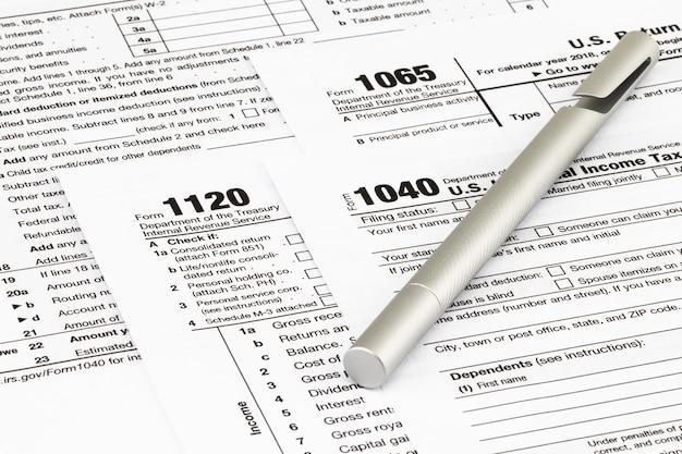 Formularze podatkowe z pieniędzmi i długopisem.