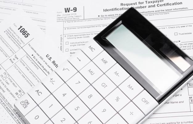 Formularze podatku dochodowego z długopisem i kalkulatorem