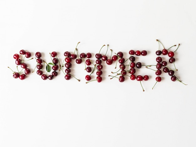 Formułuje lato tworzył od świeżej dojrzałej czereśniowej jagody na białym tle. widok z góry. kopia przestrzeń