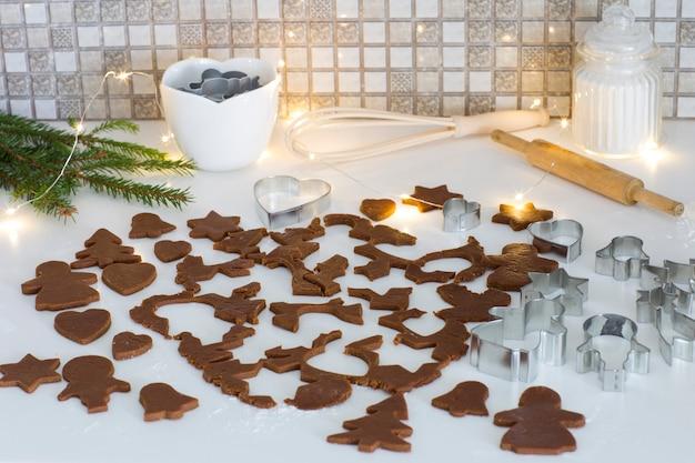 Formy do pieczenia, rozwałkowane ciasto na pierniczki, mąkę, girlandę i wałek do ciasta
