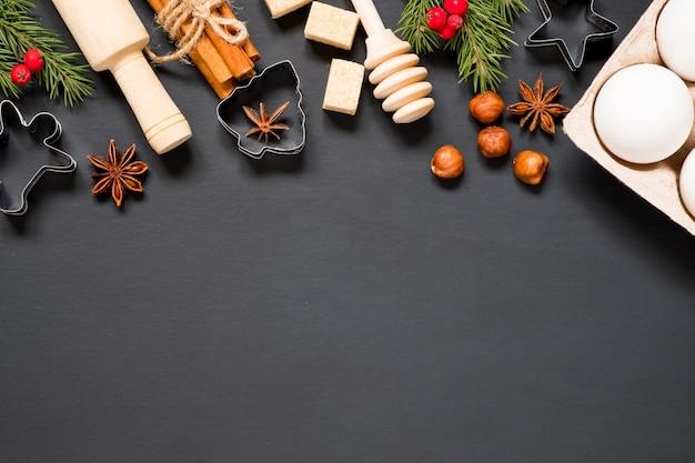 Formy i składniki do robienia ciasteczek świątecznych na czarnym tle