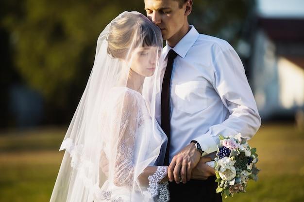 Fornal i panna młoda w białej sukni na tle natury. fotografia ślubna. szczęśliwa rodzina