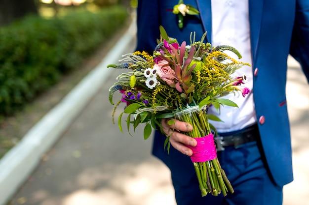 Fornal trzyma kwiatu bukiet, zamyka up elegancki fornal trzyma ślubnego bukiet