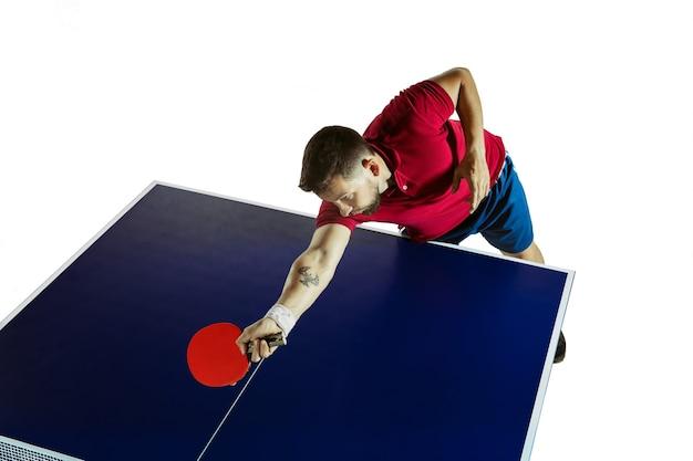 Forsowne. młody człowiek gra w tenisa stołowego na białej ścianie. modelka gra w ping ponga. pojęcie wypoczynku, sportu, ludzkich emocji w rozgrywce, zdrowego stylu życia, ruchu, akcji, ruchu.