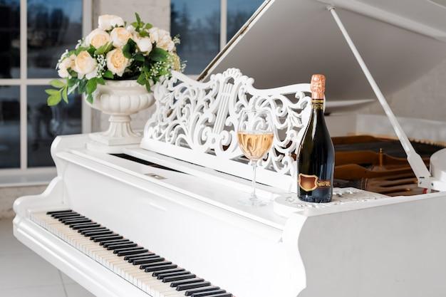 Fortepian w luksusowym białym klasycznym wnętrzu z winem, palmami i kwiatami.