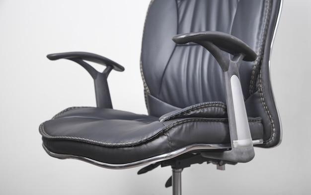 Fotel biurowy z czarnej skóry na szarym tle.