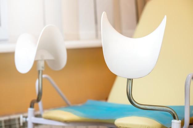 Fotel ginekologiczny w gabinecie ginekologicznym na pomarańczowym tle kontrola zdrowia