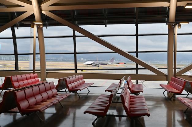 Fotel pasażerski lotniska i samolot, widok z terminalu lotniska.