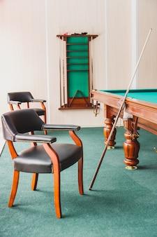 Fotel, stół bilardowy, kij w sali bilardowej. przygotowanie do gry