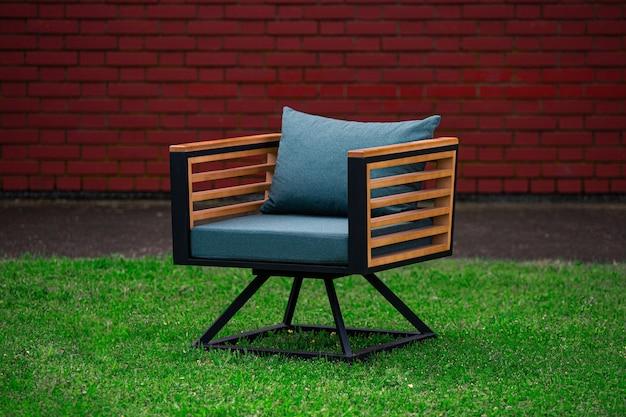 Fotel w stylu loftu z niebieskimi poduszkami, meble na trawniku