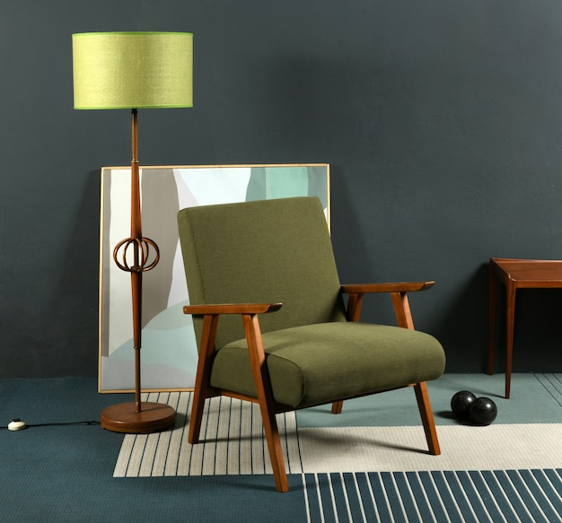 Fotel w stylu retro z lat 70. umieszczony na dywanie w pobliżu lampy i abstrakcyjny obraz na szarej ścianie