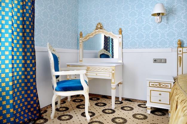 Fotel w stylu vintage w jasnym klasycznym wnętrzu z komodą i lustrem