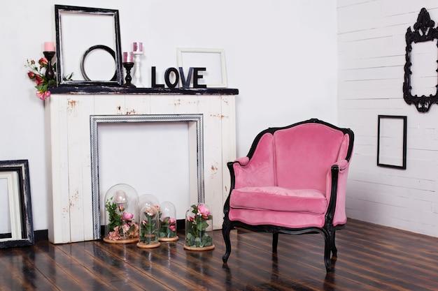 Fotel welurowy w stylu vintage, w jasnym pokoju i sztucznym kominku. poddasze wewnętrzne z drewnianymi białymi ścianami. pokój w stylu gotyckim.