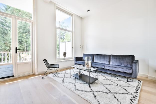 Fotele i sofa ustawione wokół stołu w jasnym salonie nowoczesnego domu
