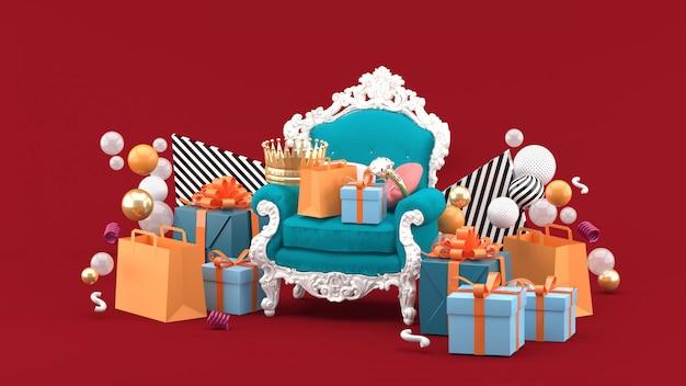 Fotele, korony, pierścionki i prezenty pośród kolorowych kulek na czerwono. renderowania 3d.