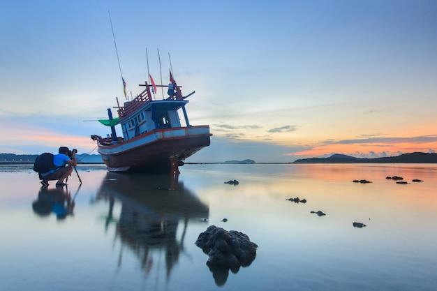 Fotograf bierze zdjęcie wschód słońca na plaży rawai w phuket w tajlandii