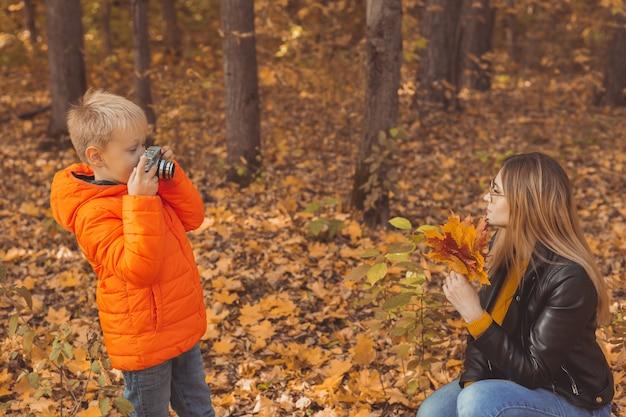 Fotograf chłopiec robi zdjęcia matce w parku w jesienne hobby fotografia sztuka i rozrywka