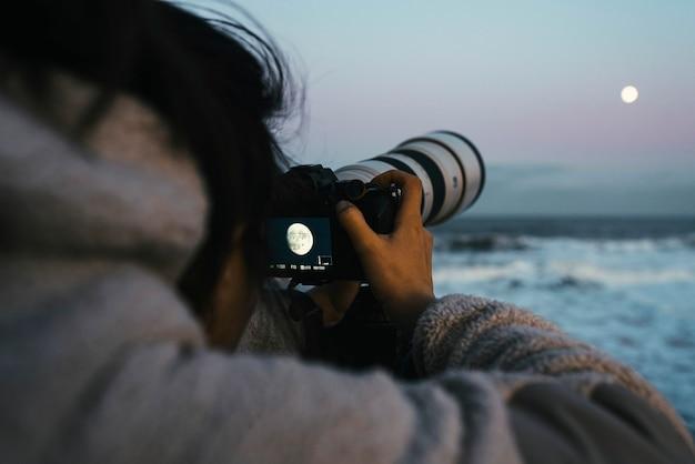 Fotograf chwytający księżyc nad morzem