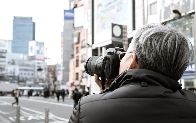Fotograf dla dorosłych, dziennikarz, podróżujący, robi zdjęcie budynku billboardu lub biznesu na neonowej ulicy handlowej w dzielnicy shinjuku w tokio, japonia