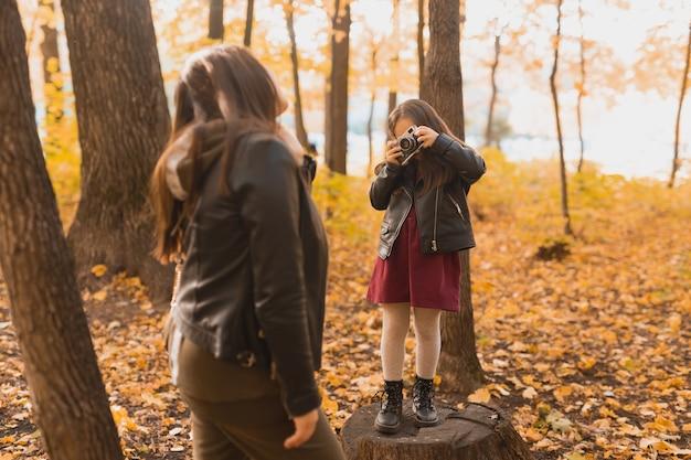Fotograf dla dziewczynki robi zdjęcia matce w parku w jesienne hobby i sztuka fotograficzna