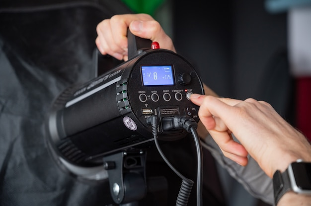Fotograf dostosowuje natężenie światła softboxa w studio. mężczyzna ustawiający sprzęt fotograficzny szykując się do sesji zdjęciowej.