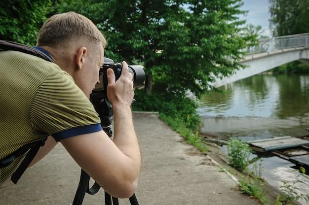Fotograf fotografujący ze statywem tło mostu
