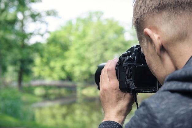 Fotograf fotografujący ze statywem w tle mostu