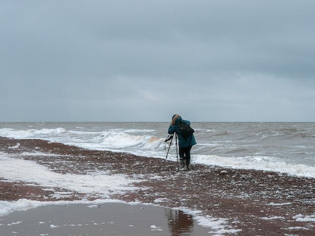 Fotograf fotografuje krajobraz na brzegu szalejącego północnego morza w trudnych warunkach.