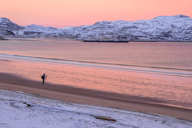 Fotograf fotografuje wspaniały arktyczny krajobraz o zachodzie słońca nad morzem barentsa.