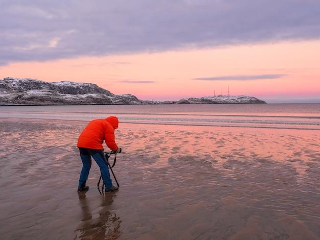 Fotograf fotografuje wspaniały arktyczny krajobraz o zachodzie słońca nad oceanem arktycznym.
