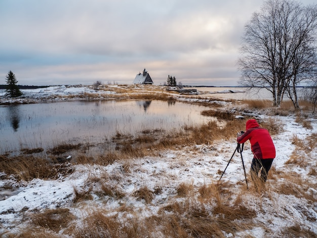 Fotograf fotografuje wspaniały śnieżny zimowy krajobraz z autentycznym domem na brzegu w rosyjskiej miejscowości rabocheostrovsk. rosja