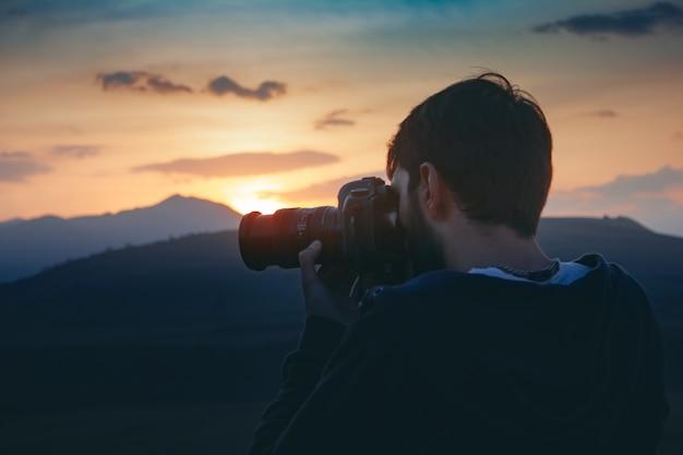 Fotograf fotografuje zachód słońca w górach