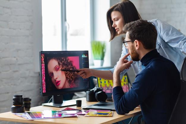 Fotograf i grafik pracujący w biurze z laptopem, monitorem, tabletem graficznym i paletą kolorów.