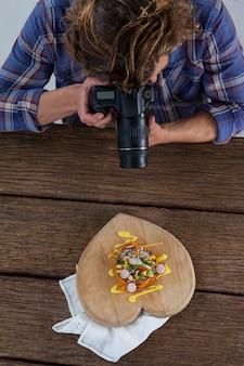 Fotograf klikający zdjęcie jedzenia aparatem cyfrowym