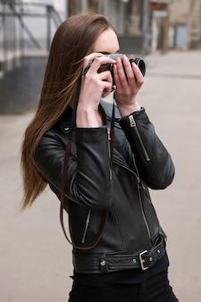 Fotograf kobieta. elektronika starej szkoły. piękna osoba ze sztuki, tło do sesji zdjęciowej, aparat retro, kreatywne hobby dla młodych ludzi