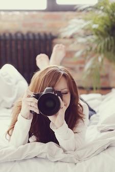 Fotograf kobieta leżąc w łóżku z aparatu fotograficznego