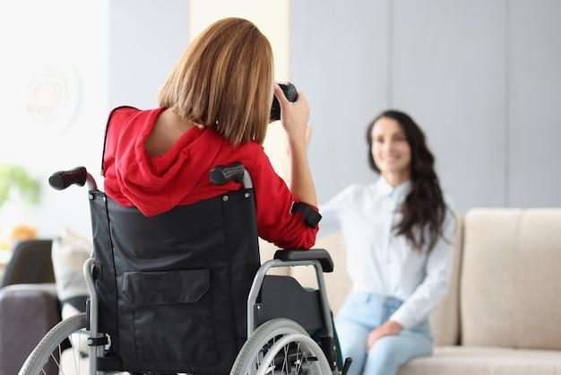 Fotograf kobieta na wózku inwalidzkim fotografuje model w studio fotograficznym z bliska. społeczna adaptacja koncepcji osób niepełnosprawnych.