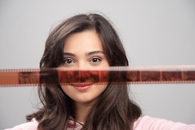 Fotograf kobieta patrząc na przezroczy na szarej ścianie.