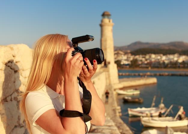 Fotograf kobieta-podróżniczka z profesjonalnym aparatem robi zdjęcie retimno, kreta, grecja.