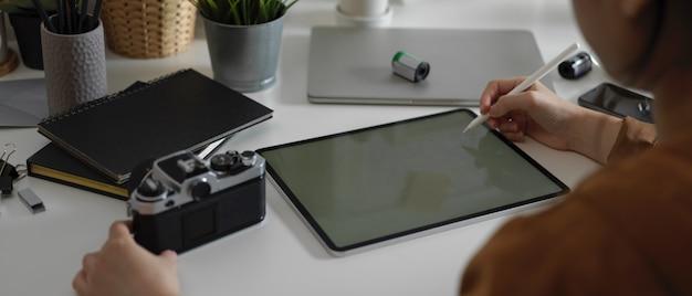Fotograf kobieta pracuje nad makietą tabletu z rysikiem i aparatem na stole z dostawami w studio