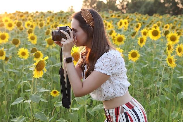 Fotograf kobieta robi zdjęcia w przyrodzie, fotograf robi zdjęcia pięknego pola słoneczników o zachodzie słońca. wysokiej jakości zdjęcie