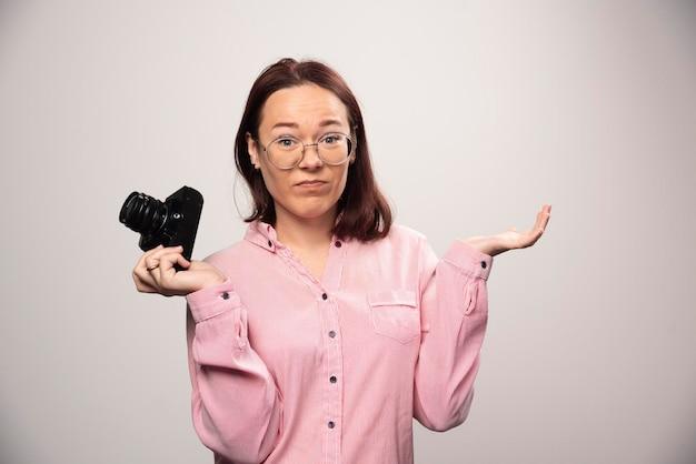 Fotograf kobieta trzyma aparat na białym. zdjęcie wysokiej jakości