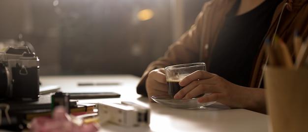 Fotograf kobieta trzymając filiżankę kawy siedząc przy stole roboczym z aparatem i dostawami w studio
