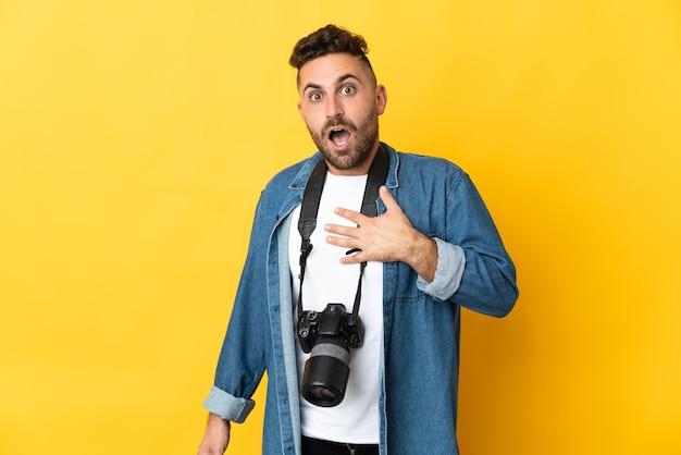 Fotograf mężczyzna na białym tle na żółtym tle zaskoczony i zszokowany, patrząc w prawo