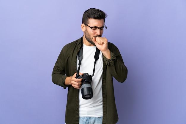 Fotograf mężczyzna nad odosobnioną purpurową ścianą dużo kaszle