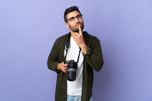 Fotograf mężczyzna nad odosobnionym fioletem mając wątpliwości podczas patrzenia w górę