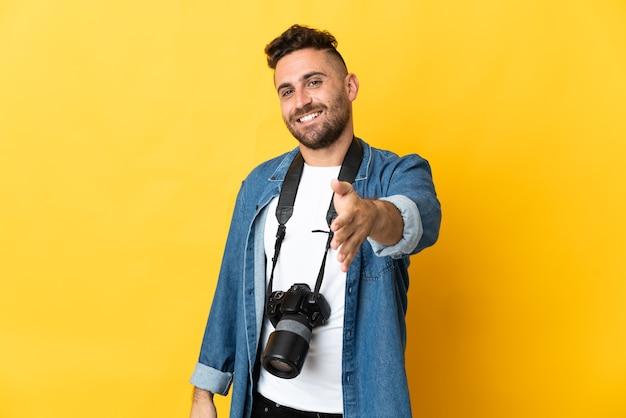 Fotograf mężczyzna odizolowany na żółtym tle, ściskając ręce za zamknięcie dobrej oferty