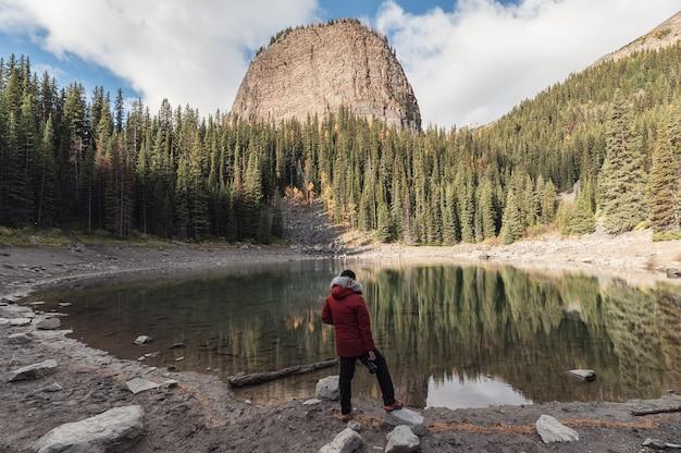 Fotograf mężczyzna stojący nad jeziorem mirror w jesiennym lesie w pobliżu jeziora louise w parku narodowym banff, kanada